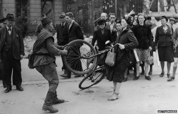 Ruski vojnik nakon oslobađanja Berlina otima biciklo od Njemice.